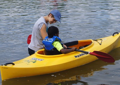 Casey helping a youth at her summer camp experience kayaking for the first time.