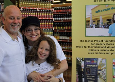 Joshua and his parents celebrate the launch of The Joshua Project at a Whole Foods store.