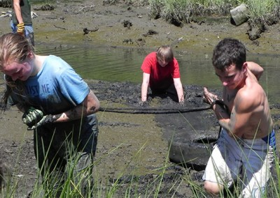 James - Dragging a tire out of the mud with a fellow volunteer during Clean the Bay day.