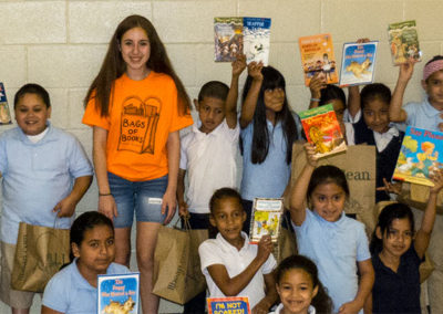 Alexa with students showing off their new books.