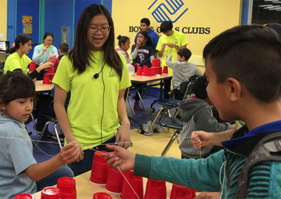 Sharleen challenging kids to build towers out of red Solo cups without their hands.